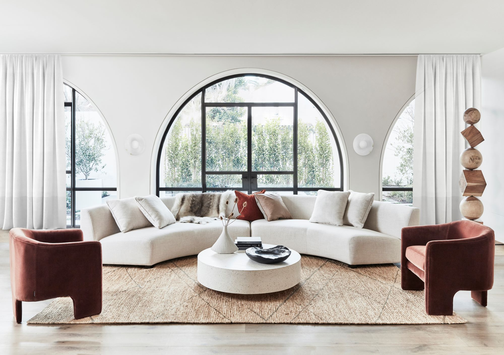 Coco Republic living room styled with sofa and two blush occasional chairs